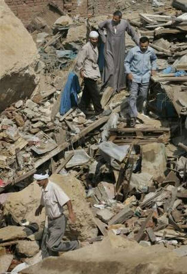 Residents walk through the rubble of a devastated shantytown outside Cairo on Sunday, one day after a rock slide killed 32 and trapped hundreds. Photo: BEN CURTIS, ASSOCIATED PRESS