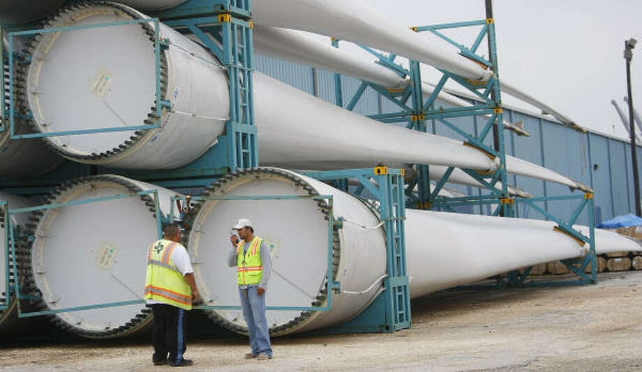 The blades of wind turbines dwarf terminal workers at the Port of Houston. Parts of wind turbines are unloaded from ships at the GP Terminal. Photo: Mayra Beltran, Chronicle