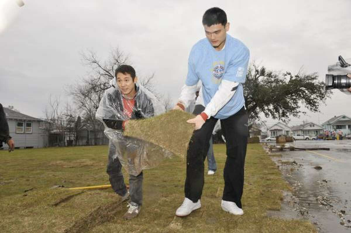 Rockets center Yao Ming and actor Jet Li help with landscaping work at the