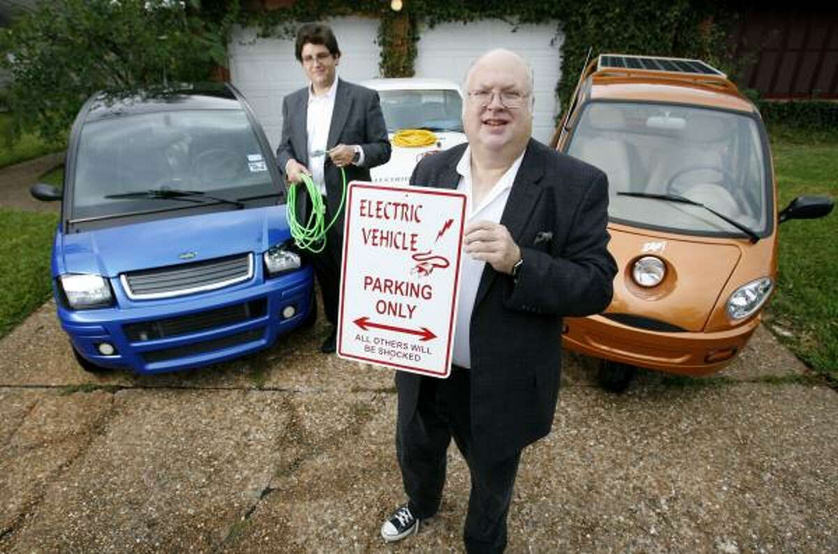 Dale Brooks, foreground, is so high on electric cars that he has three. He and his friend Steve Mathis, standing ready with an extension cord, belong to the Houston Electric Auto Association.