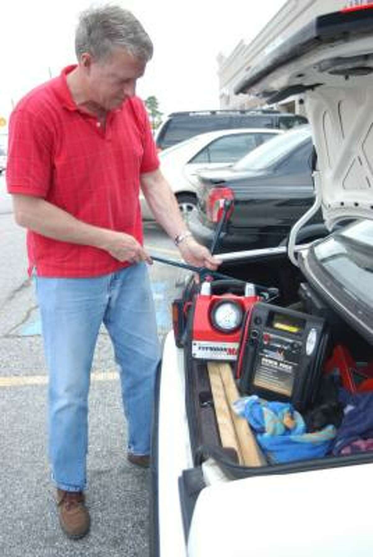 Walt Brinker shows a few of the tools he uses to help stranded motorists. He has been assisting stranded motorists for about six years.