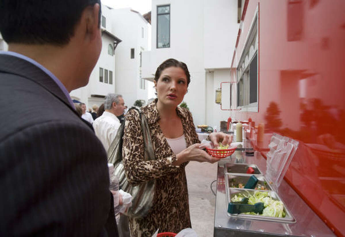 Alia Rdissi puts lettuce on her taco as she talks with business associate Steve Lee near the Armando's taco truck at a party at new condos at 207 Reinerman.
