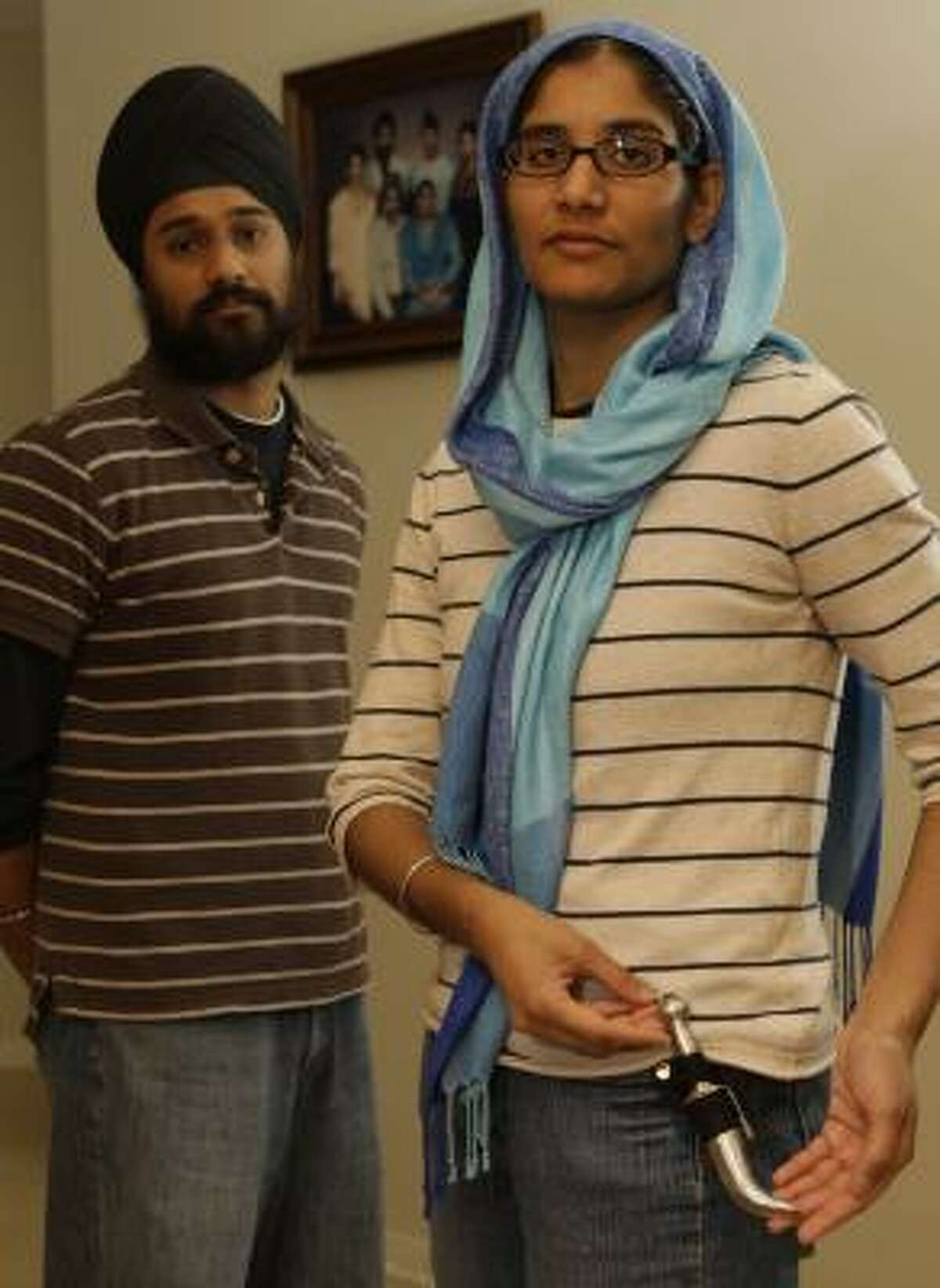 Kawaljeet Kaur, with her brother, Ramandeep Singh, shows her Kirpan, a ceremonial dagger required by the Sikh faith. Deputies handcuffed family members after they reported a burglary at their home.