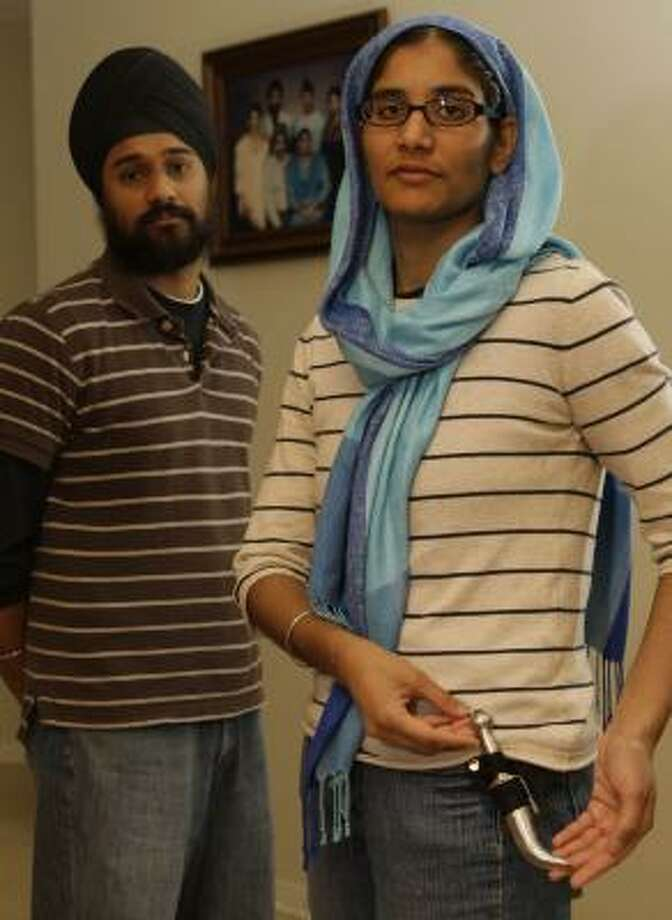 Kawaljeet Kaur, with her brother, Ramandeep Singh, shows her Kirpan, a ceremonial dagger required by the Sikh faith. Deputies handcuffed family members after they reported a burglary at their home. Photo: MELISSA PHILLIP, CHRONICLE