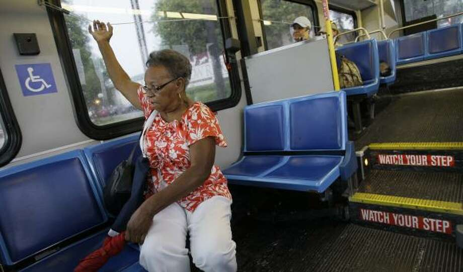 Margaret Jenkins, signaling for a stop, has to transfer four times before she gets to her part-time office job near Reliant Park. Photo: MELISSA PHILLIP, CHRONICLE