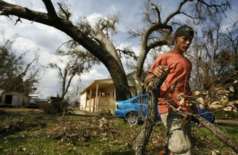 Jerrith Baird, 16, clears debris from his yard in High Island. Baird's grandmother, Jennifer Mclemore, 58, of Gilchrist remains missing after Ike. Photo: SHARON STEINMANN, CHRONICLE