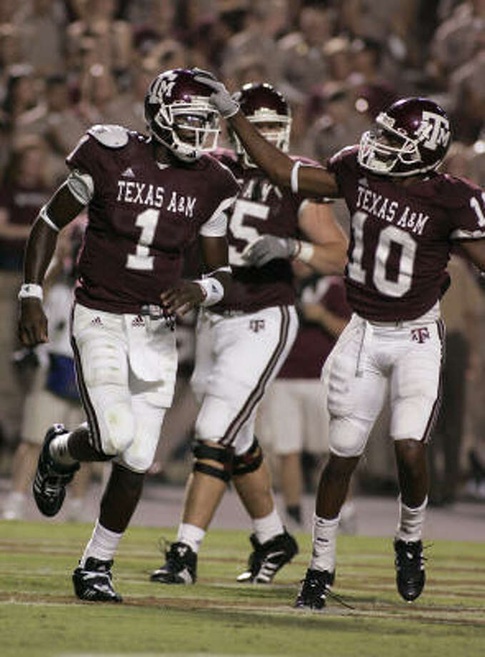 Texas A&M backup QBs Jerrod Johnson (1) and Ryan Tannehill have gone from throwing passes to catching them. Photo: Paul Zoeller, AP
