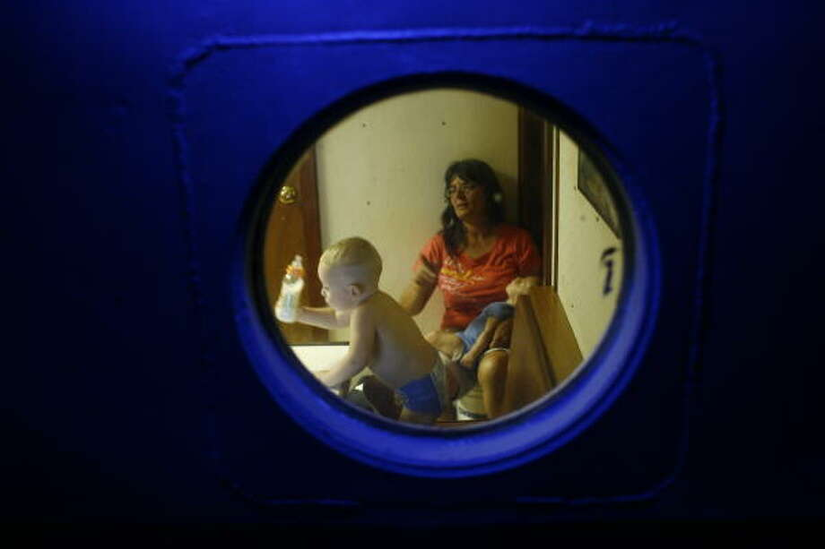 Margaret Shiver watches television and babysits her grandson Kaleb Simon, 2, in the tug boat where she and her husband, Steve Shiver, are living in Oak Island. Photo: Sharon Steinmann, Houston Chronicle