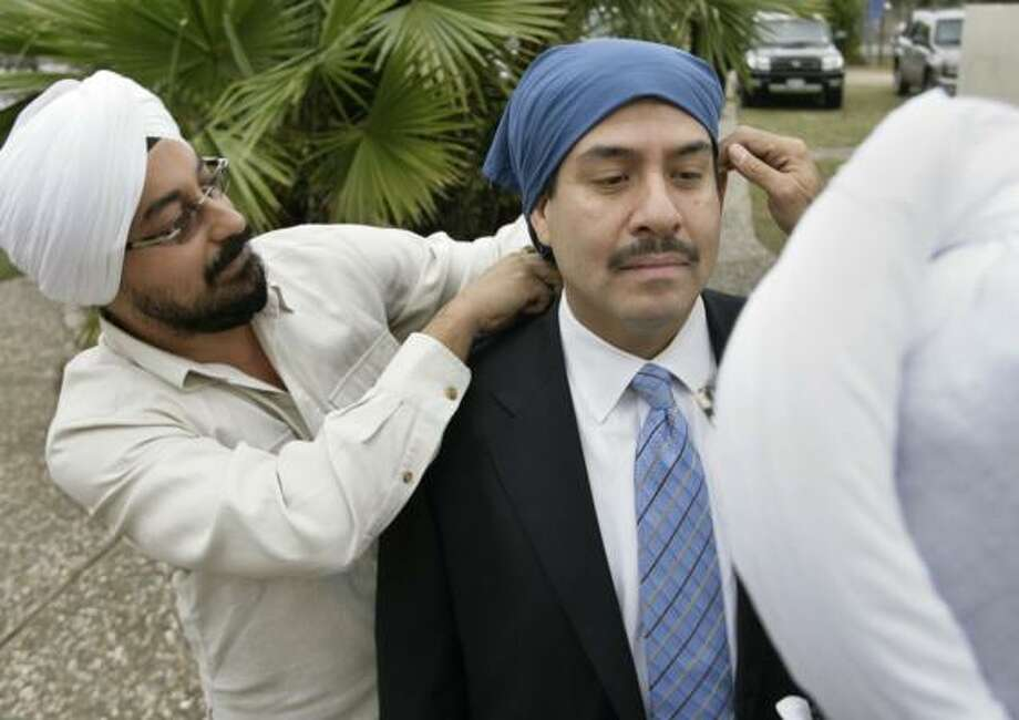 Sheriff-elect Adrian Garcia gets help adjusting a head covering he wore while addressing Sikh followers at the Sikh Center of Houston on Sunday. Photo: Eric Kayne, Chronicle