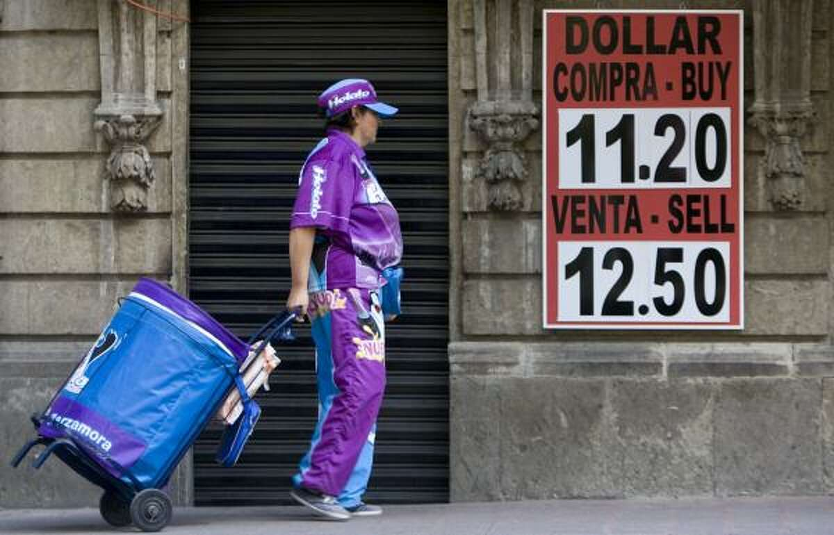 An ice-pop vendor passes a money exchange house in Mexcio City. On Friday, Mexico's government spent $6.4 billion from its dollar reserves to buy pesos in an attempt to shore up the currency.