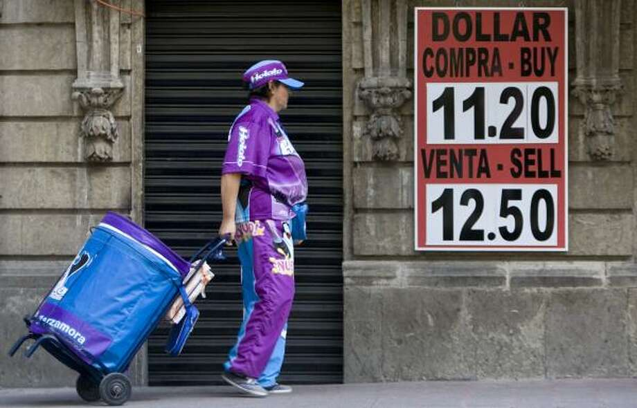 An ice-pop vendor passes a money exchange house in Mexcio City. On Friday, Mexico's government spent $6.4 billion from its dollar reserves to buy pesos in an attempt to shore up the currency. Photo: EDUARDO VERDUGO, ASSOCIATED PRESS
