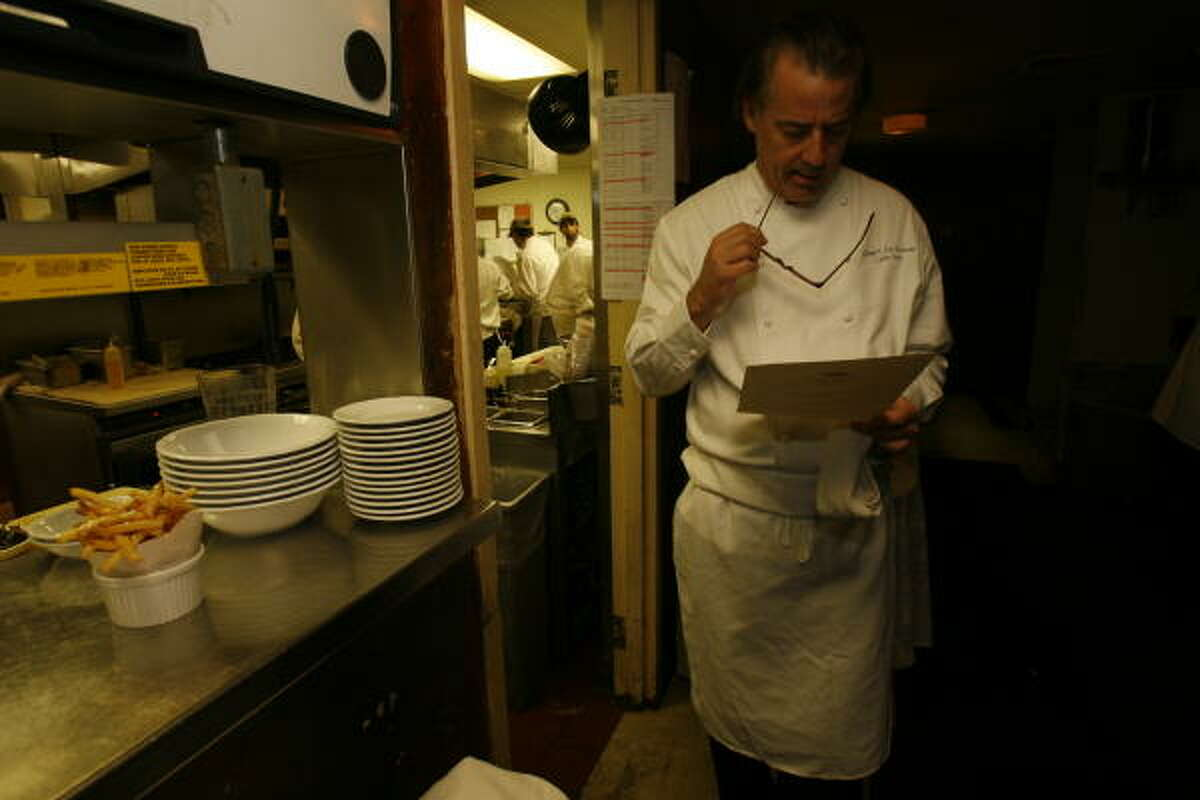 Chef Robert Del Grande looks over a list of dishes ordered by a party at Cafe Annie. Del Grande is the only chef in Houston to win the James Beard Award as Best Chef of the Southwest.