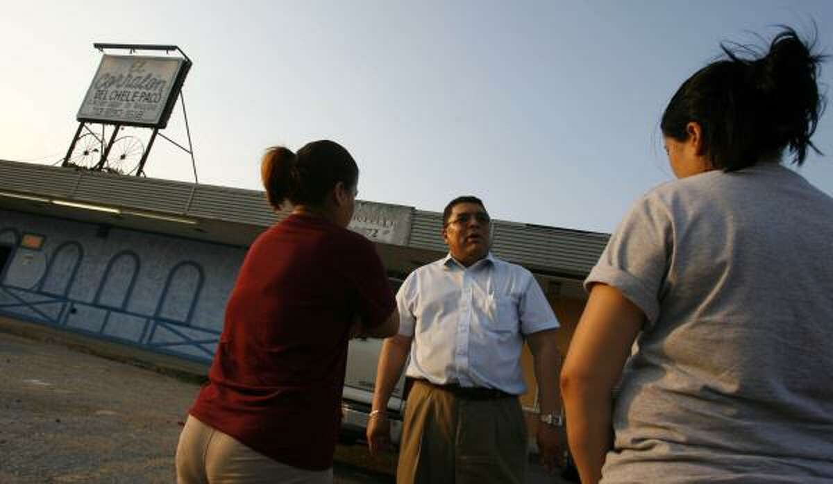 Jose Benitez, a Houston labor organizer, talks with two women who were victims of sex trafficking outside El Corralon del Chele Paco, a Houston bar targeted in the past for such trafficking.