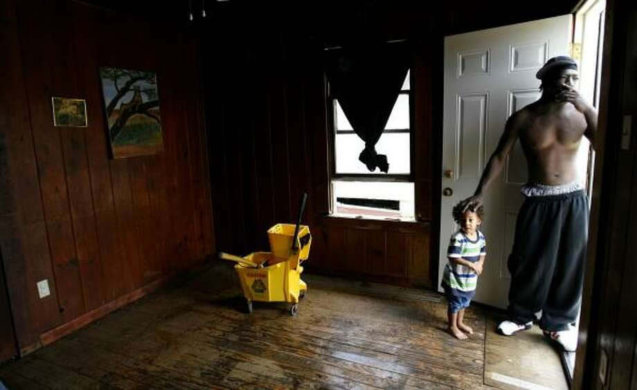 Michael Jackson with his son, Howard, 2, stands in Howard's room, damaged by Hurricane Ike, in the Fifth Ward on Tuesday. Photo: KAREN WARREN, CHRONICLE