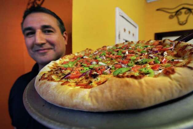 The Express-News Taste team has the cure for your pizza craving. The following restaurants have the most memorable pies. Fred Nunez holds a large Chicken Enchilada Pizza at Alamo Pizza, 3938 South Zarzamora. www.alamopizza.net Photo: BOB OWEN, SAN ANTONIO EXPRESS-NEWS / rowen@express-news.net