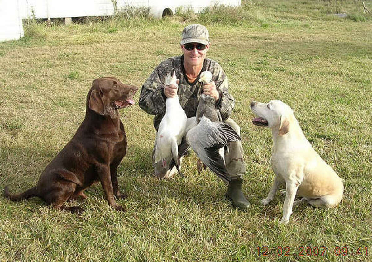 Perry Price is shown in a Dec. 2 photo with Arthur, the chocolate Labrador retriever that apparently discharged the gun, and yellow Lab, Leon.