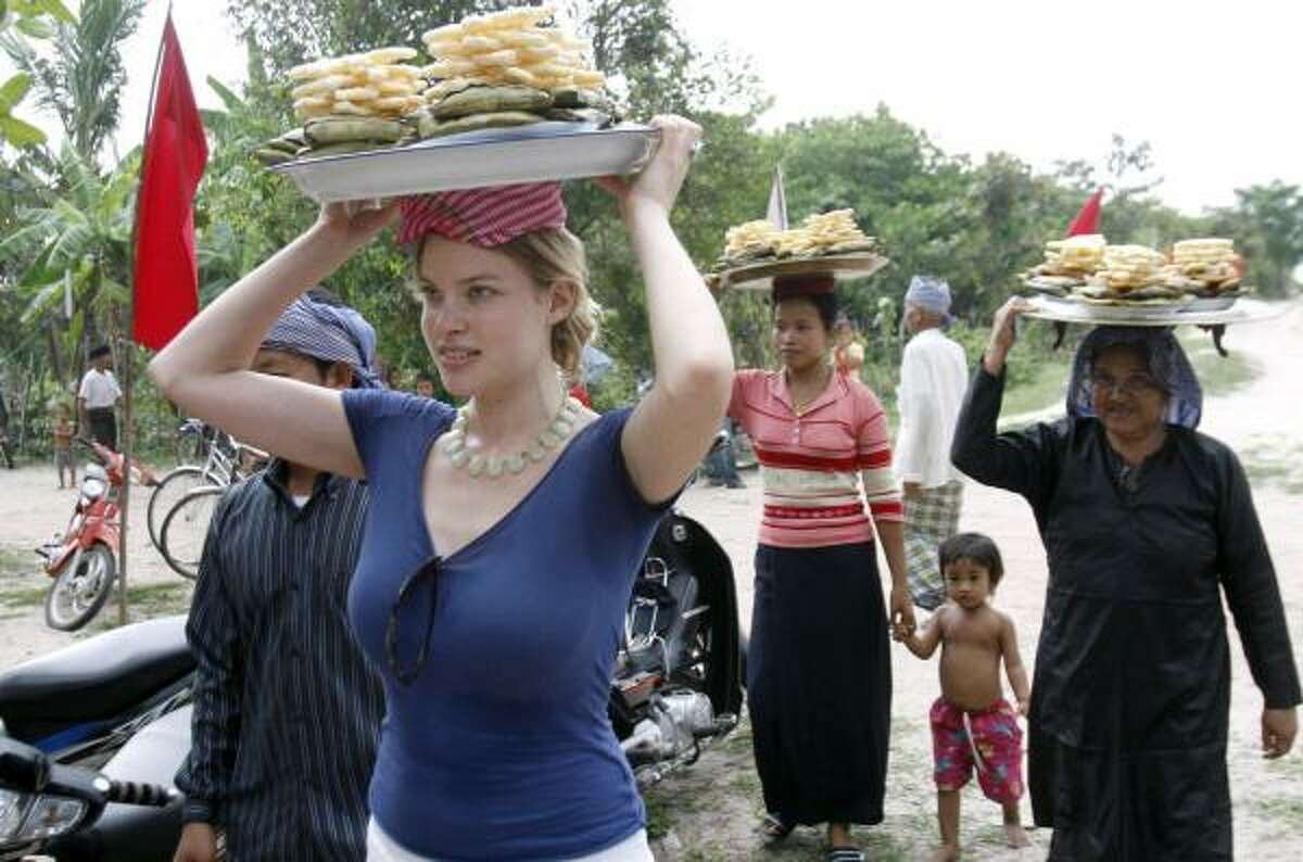 Elyse Lightman, left, carries traditional Muslim cake on her head as she makes her way to a ceremony to inaugurate a mosque at Tramoung Chrum village, Cambodia.
