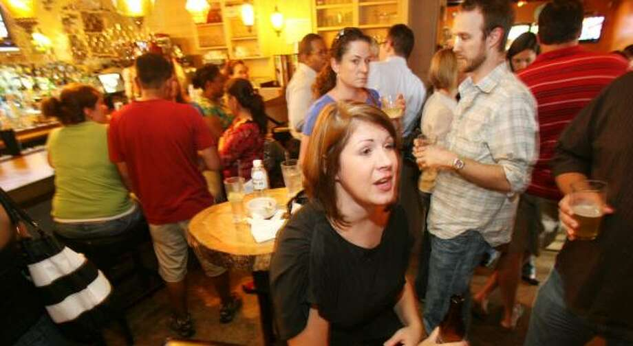Monica Danna networks over drinks at Beaver's Ice House during the Green Drinks Night social gathering for people interested in the environment and alternative energy. Photo: BILLY SMITH II, CHRONICLE