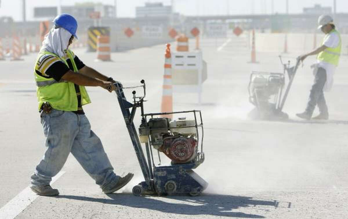 Christian Jasso, left, and other workers prepare the Katy Freeway's road surface for striping Saturday near the HOV exit for Addicks Park & Ride.