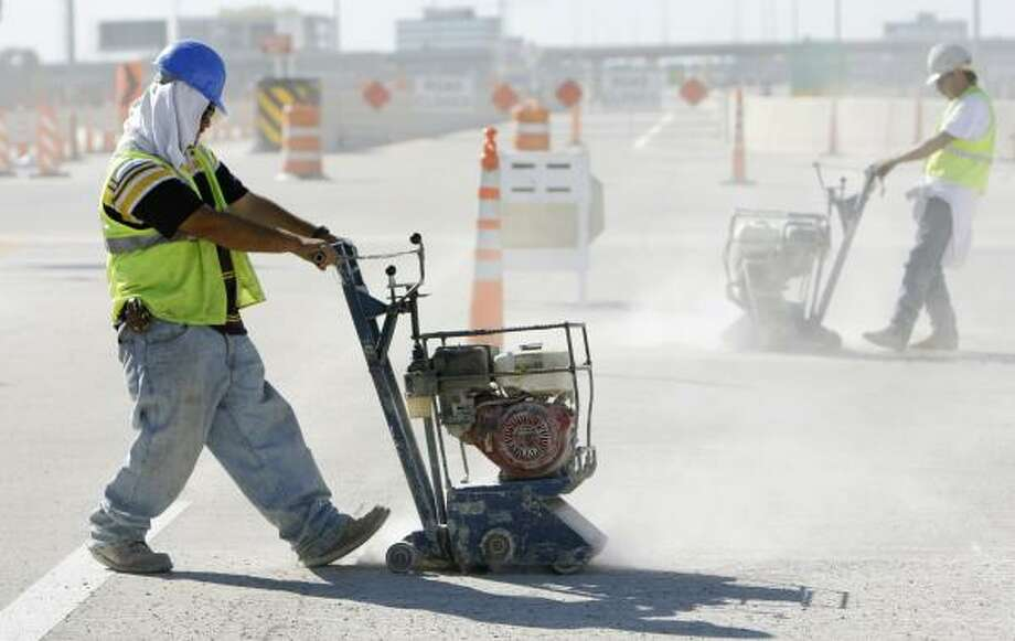 Christian Jasso, left, and other workers prepare the Katy Freeway's road surface for striping Saturday near the HOV exit for Addicks Park & Ride. Photo: MELISSA PHILLIP, CHRONICLE
