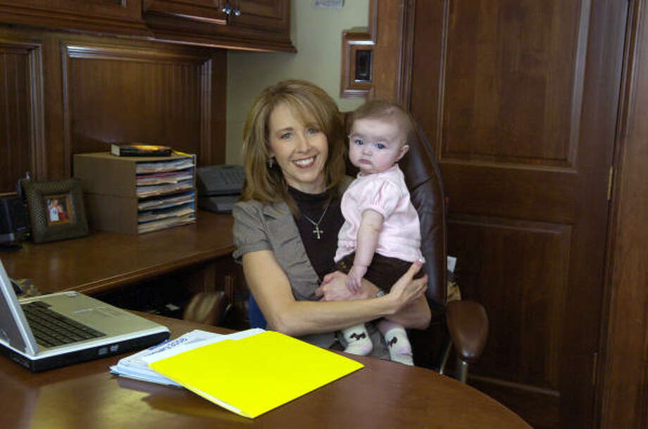 Lesley Spencer Pyle, founder of HireMyMom.com and founder and president of Home-Based Working Moms, was taking care of business with her 5- month-old daughter, Peytyn, from her office at her home in Benders Landing in Spring. Photo: Jerry Baker, For The Chronicle