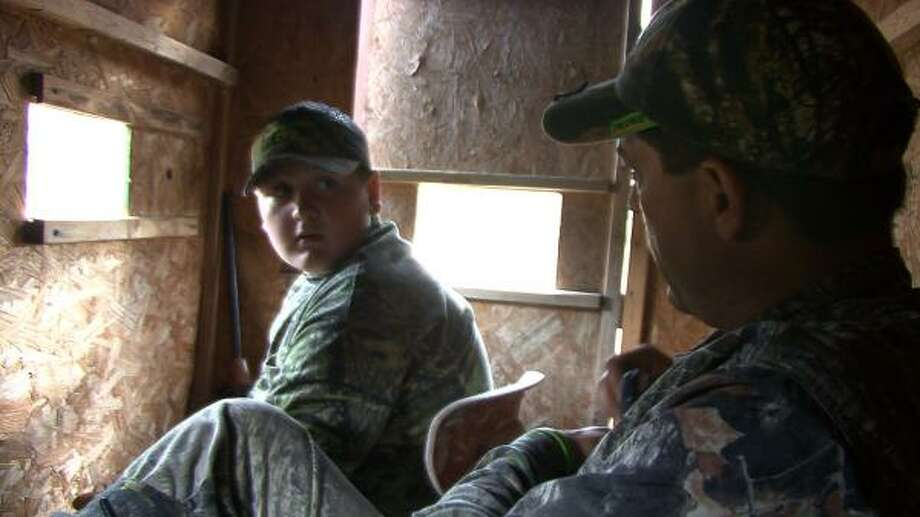 Dalton Penrod, 12, talks with Greg Flores of Cross Trail Outfitters in a hunting blind during an outing. Cross Trail Outfitters is a San Antonio-based hunting ministry aimed at boys and young men. Photo: BILLY CALZADA PHOTOS, SAN ANTONIO EXPRESS-NEWS