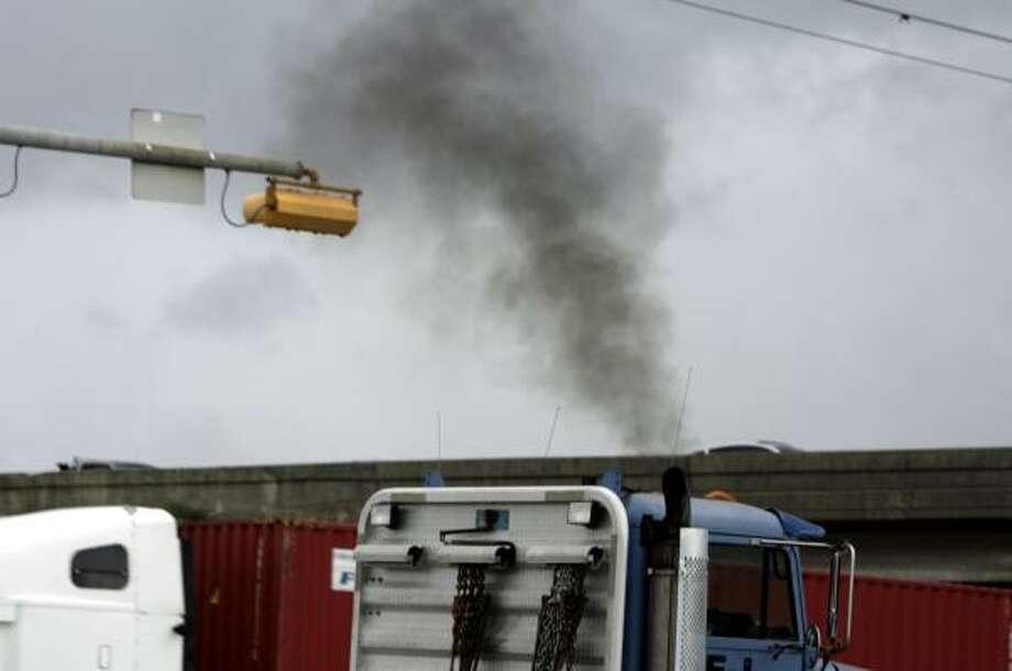 Diesel trucks rumble by on Wallisville Road and North Loop Freeway East last week. Diesel engines are a major source of soot. Photo: ERIC KAYNE, HOUSTON CHRONICLE