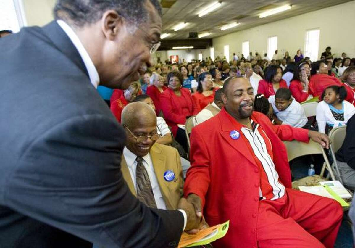 County Commissioner El Franco Lee, left, who is seeking re-election, shakes hands with Nathaniel Crump after answering questions during a meeting of The Metropolitan Organization on Sunday in the social hall of Immaculate Conception Church.