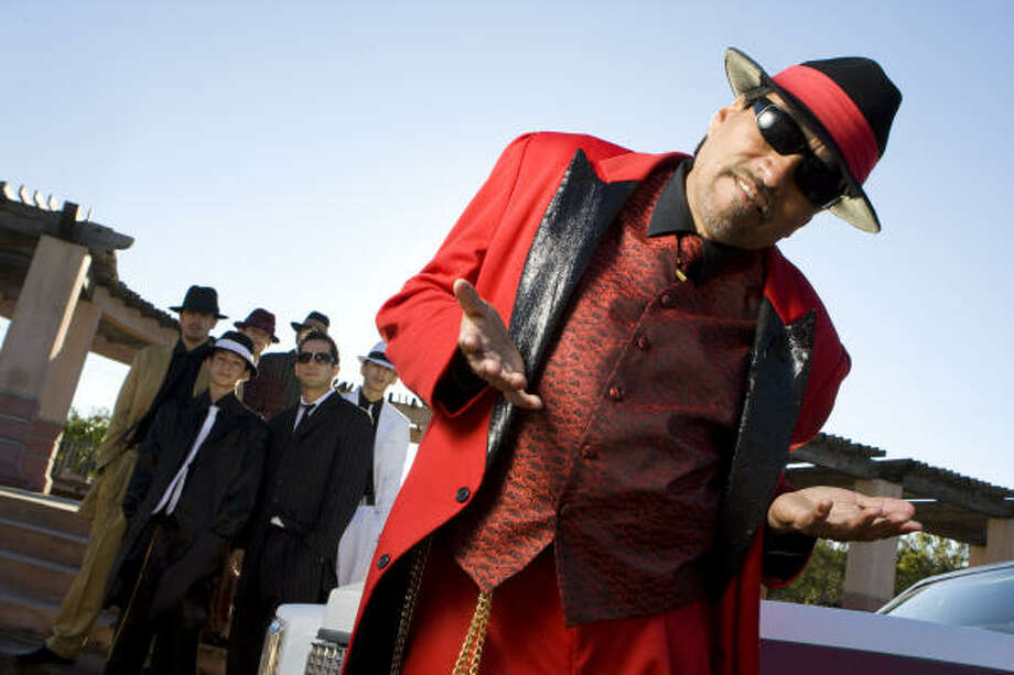 "In Houston, Richard Reyes' version of Pancho Claus wears a red zoot suit, fronts a swing band and keeps an entourage of ""elves"" and lowrider cars. Photo: Nick De La Torre, HOUSTON CHRONICLE"