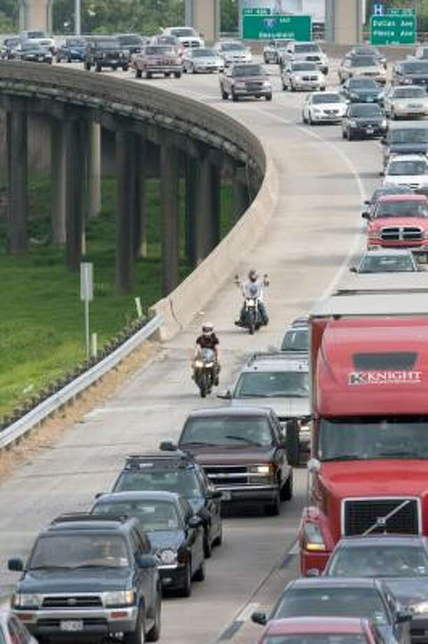 Motorcyclists competing for space on Houston's freeways sometimes make their own lanes, as these two do on Interstate 45 North near Quitman. Photo: STEVE CAMPBELL, CHRONICLE