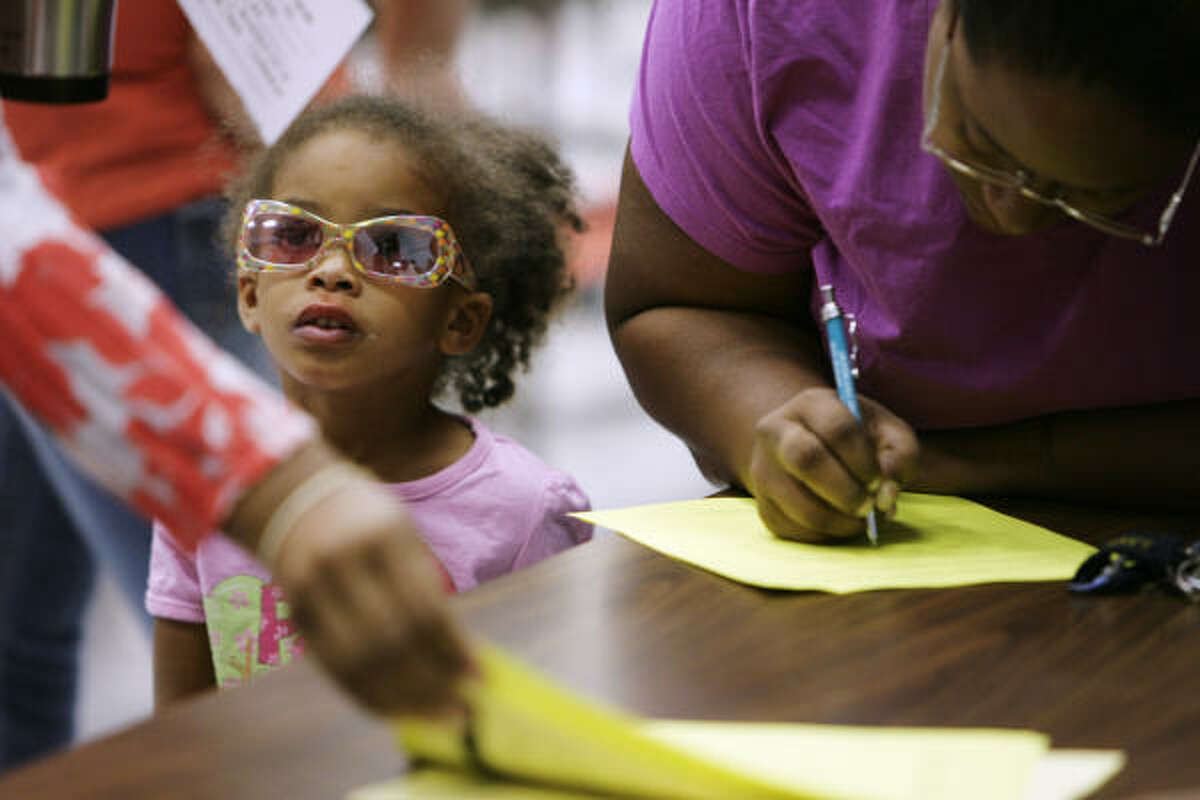 Nyjala Bush, 3, keeps her mother Adrienna Fields company as Fields fills out contact information for another daughter, who previously attended Scott Elementary, but now has started at Rosenberg Elementary because of Hurricane Ike.