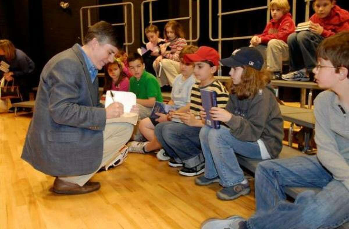 San Antonio novelist Rick Riordan signs books at a Natick, Mass., middle school last year.