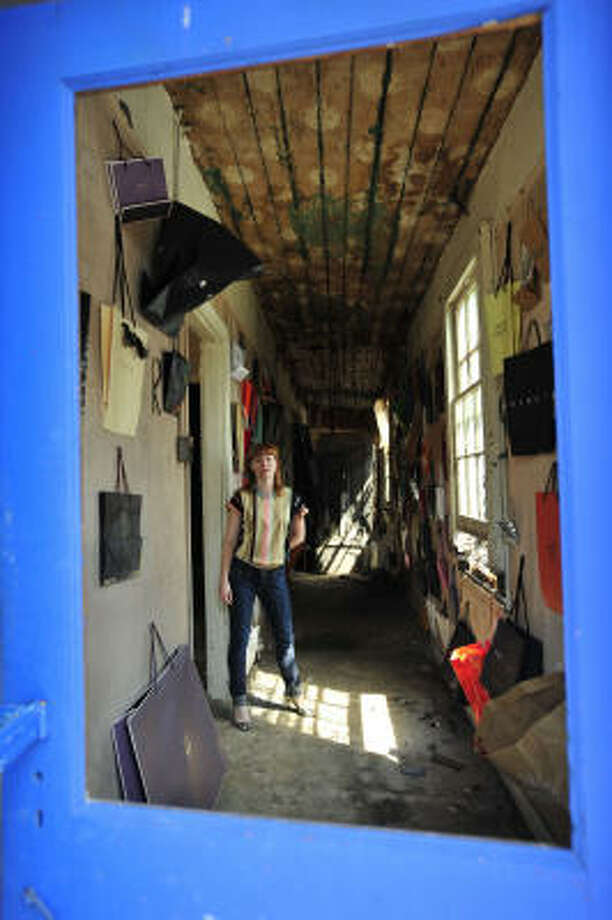 In this photo taken through the window of one of New Orleans' shotgun houses, KK Projects' Katherine Bray stands where Alton du Laney and Andre Da Costa's 1,000 Bags: A Shopping Bag Tribute to Andy Warhol and Installation of OCD Dimensions is being exhibited. It's an example of the recovery of New Orleans' art scene. Photo: Cheryl Gerber, For The Chronicle