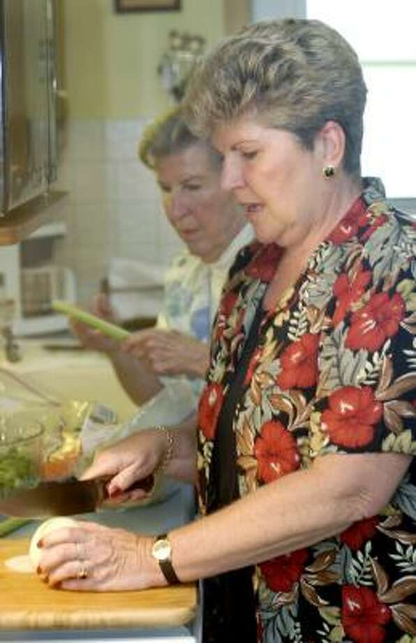 Sue Martin, right, makes dinner with her mother, Betty Gresick, at Martin's home in Claymont, Del. Gresick retired without a retirement fund, so Martin plans to work indefinitely to cover living expenses that her mother's Social Security and food stamps do not. Photo: BRADLEY C. BOWER, ASSOCIATED PRESS
