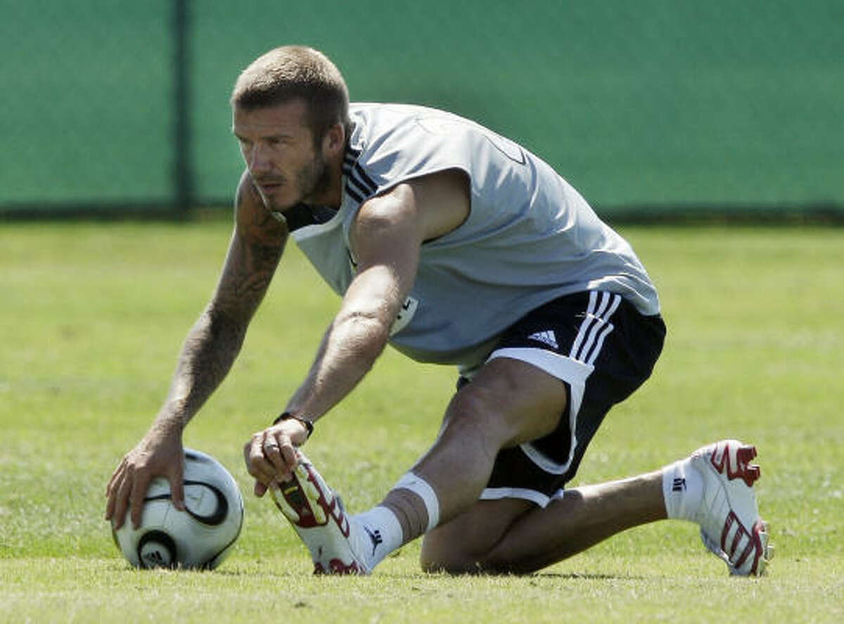 The Galaxy's David Beckham stretches his injured left ankle during practice Tuesday at Home Depot Center.