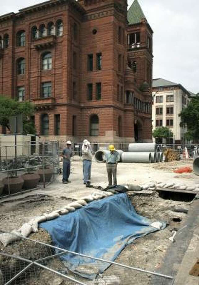 Archaeologists visit the site where artifacts dating to the Battle of the Alamo were found last week in San Antonio. Historians think the trench was used by Mexican troops for fortification. Photo: BOB OWEN, SAN ANTONIO EXPRESS-NEWS