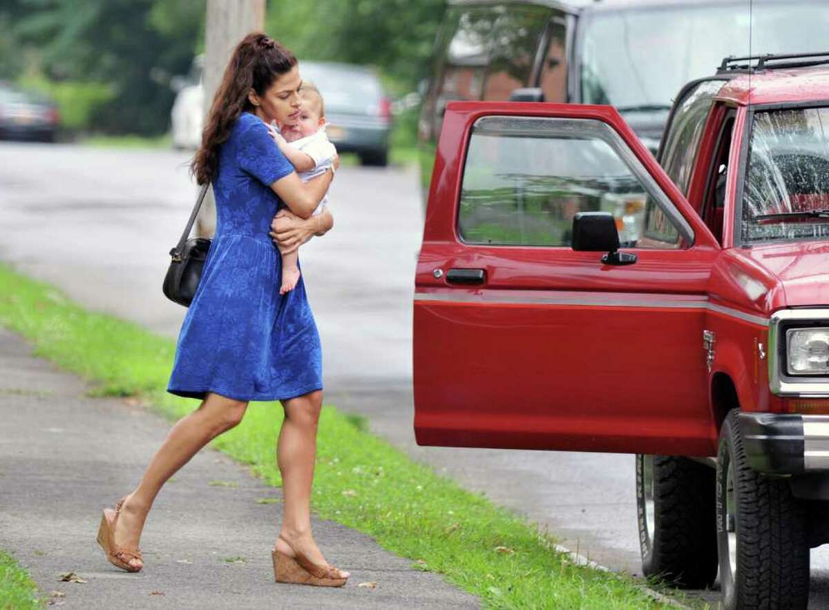 """Eva Mendes carries a baby during filming for the movie """"The Place Beyond the Pines"""" on Watt Street in Schenectady on Tuesday Aug. 9, 2011. (John Carl D'Annibale / Times Union archive)"""