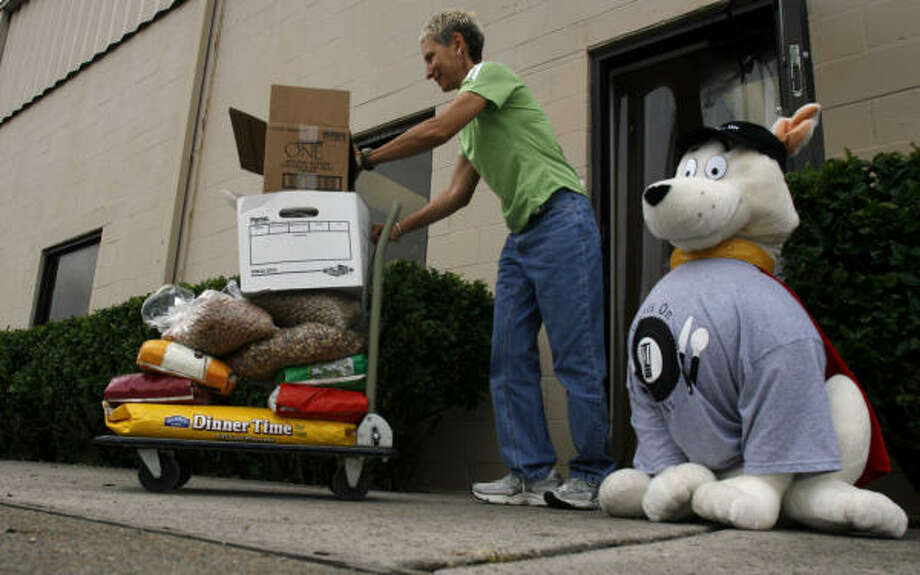 AniMeals volunteer Barbara Baldaro walks out dog and cat food to be delivered to elderly with pets in need of food on June 23 in Houston. Photo: Johnny Hanson, For The Chronicle