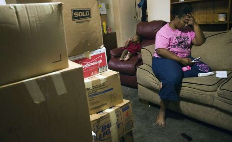 Michelle Mercadel makes phone calls in a desperate search for housing last week. The family of nine faces eviction from a one-bedroom apartment and can't find a new one large enough. Photo: SMILEY N. POOL, CHRONICLE