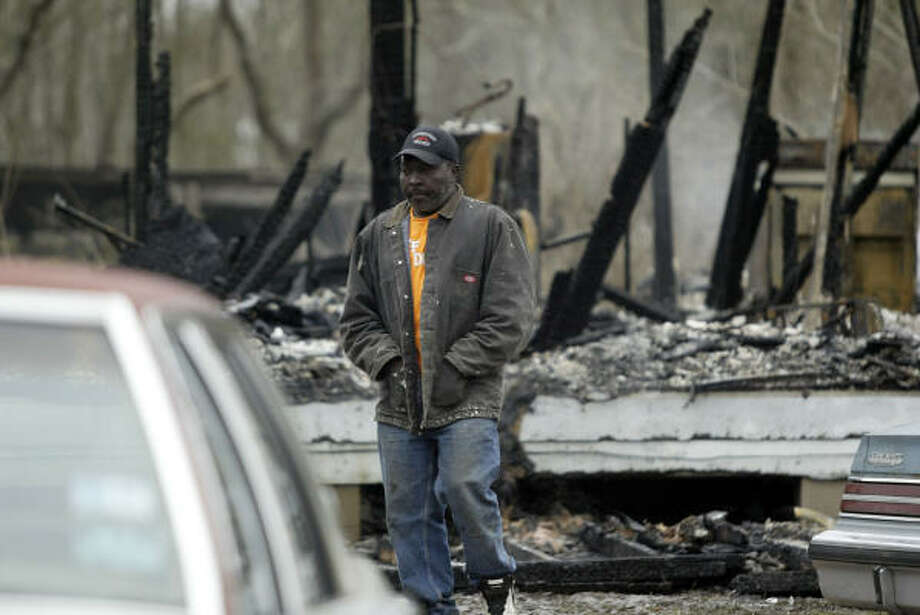 Elisha Hall, 46, walks past the ruins of the dwelling where his son, Elisha Davis, 26, died trying to rescue children who were trapped in a fire this morning. Photo: Jessica Kourkounis, For The Chronicle