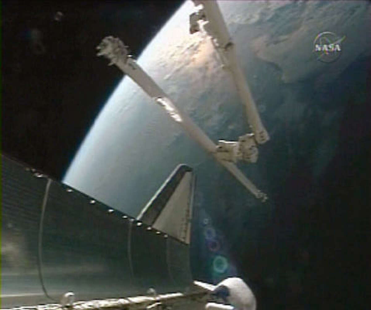 In this image from NASA TV, a boom extension for the robotic arm is moved to the shuttle Discovery from the international space station today. The extension will be used for Saturday's spacewalk by mission specialist Scott Parazynski to repair the torn solar panel.