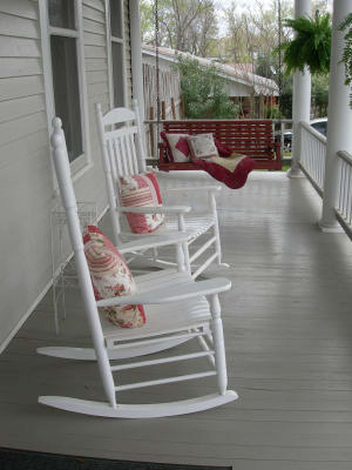Guests at Palestine's Fig Tree Manor can relax in rocking chairs on a porch. The inn combines overnight accommodations and a restaurant.