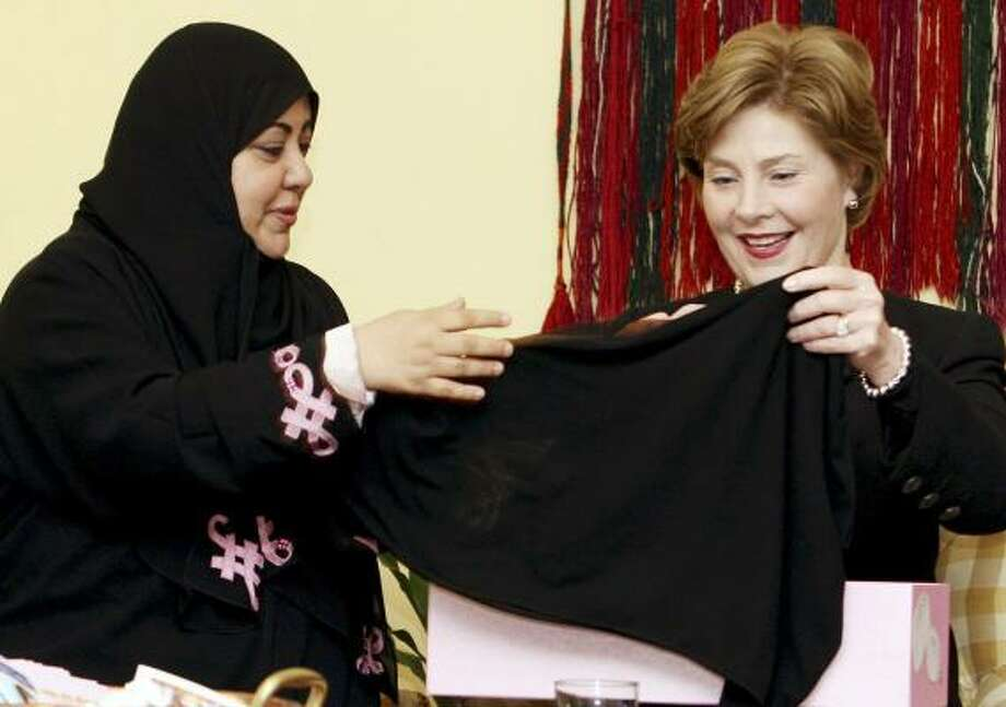 Gynecologist Samia al-Amoudi presents a headscarf to first lady Laura Bush recently to thank her for promoting breast cancer awareness in Saudi Arabia. The nation so stigmatizes women with the disease that many avoid potentially life-saving treatment early on. Al-Amoudi's breast cancer was diagnosed last year. Photo: HASAN JAMALI, AFP/GETTY IMAGES