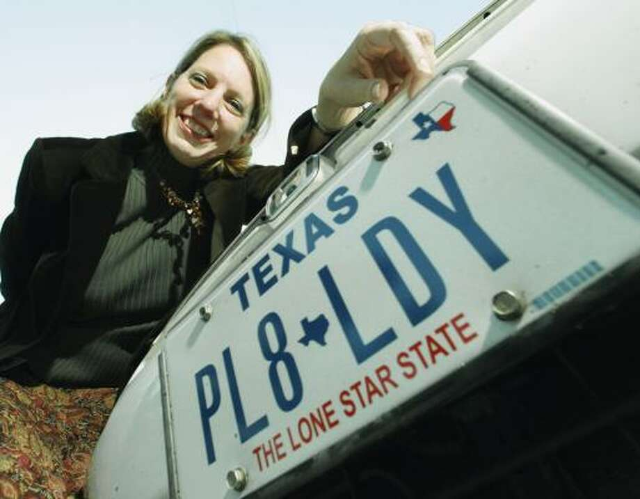 Rebecca Davio, of the state's Vehicle Titles and Registration Division, shows off her vanity license plate in Austin. Photo: Associated Press