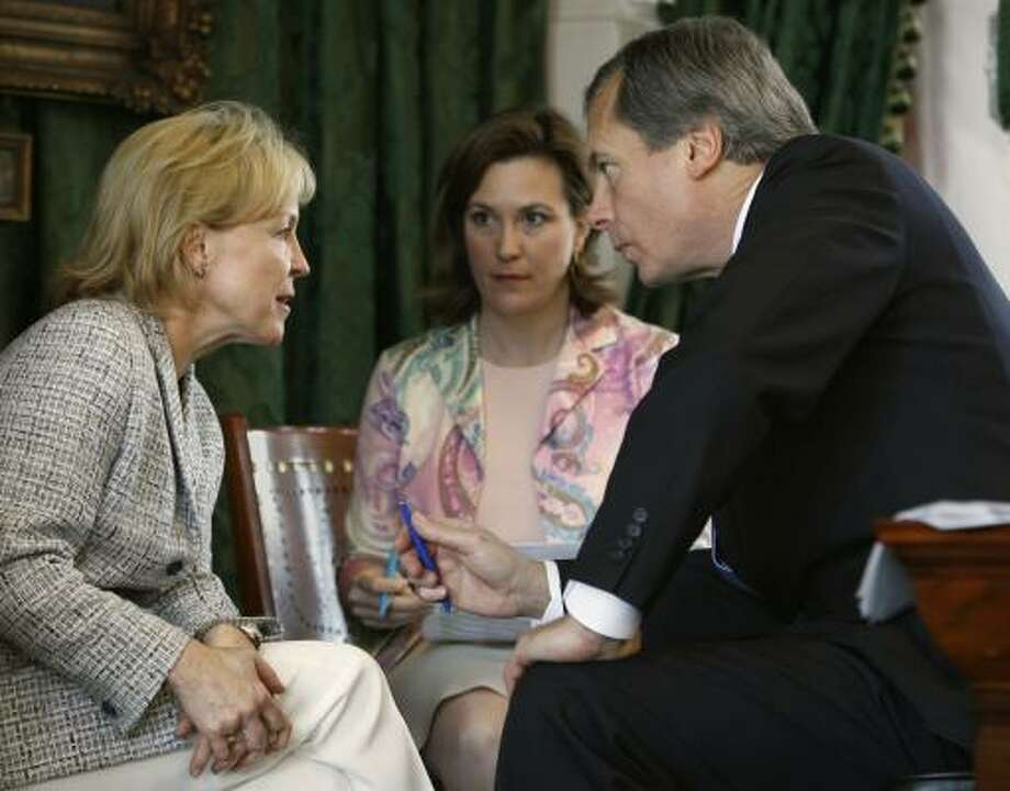 Rep. Myra Crownover, R-Denton, left, talks with Lt. Gov. David Dewhurst in the Texas Senate. Julia Rathgeber, center, is Dewhurst's director of public policy.  Photo: Harry Cabluck, AP