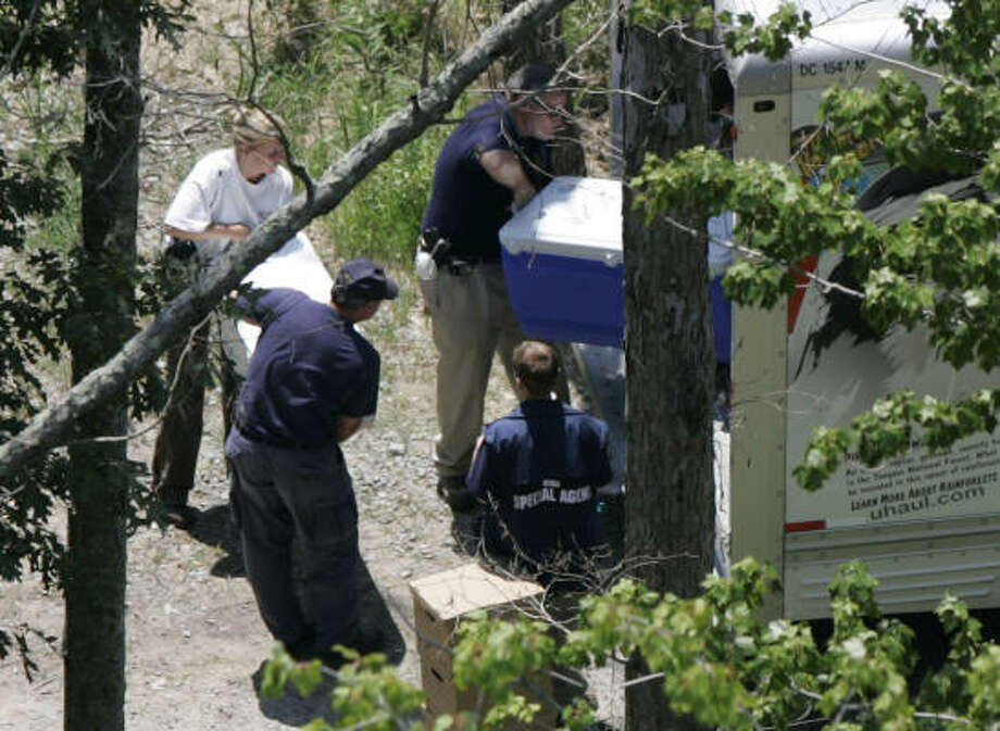 State and federal officials load coolers of evidence into a truck as they search the grounds behind a home owned by Falcons quarterback Michael  Vick in Smithfield, Va. Photo: Steve Helber, AP