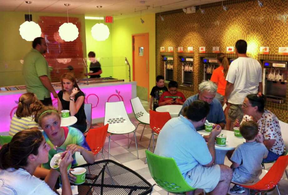 Customers enjoy frozen yogurt, fresh fruit and an array of topics at Peachwave. The shop is at 213 Greenwood Ave. in Bethel. Photo: Contributed Photo