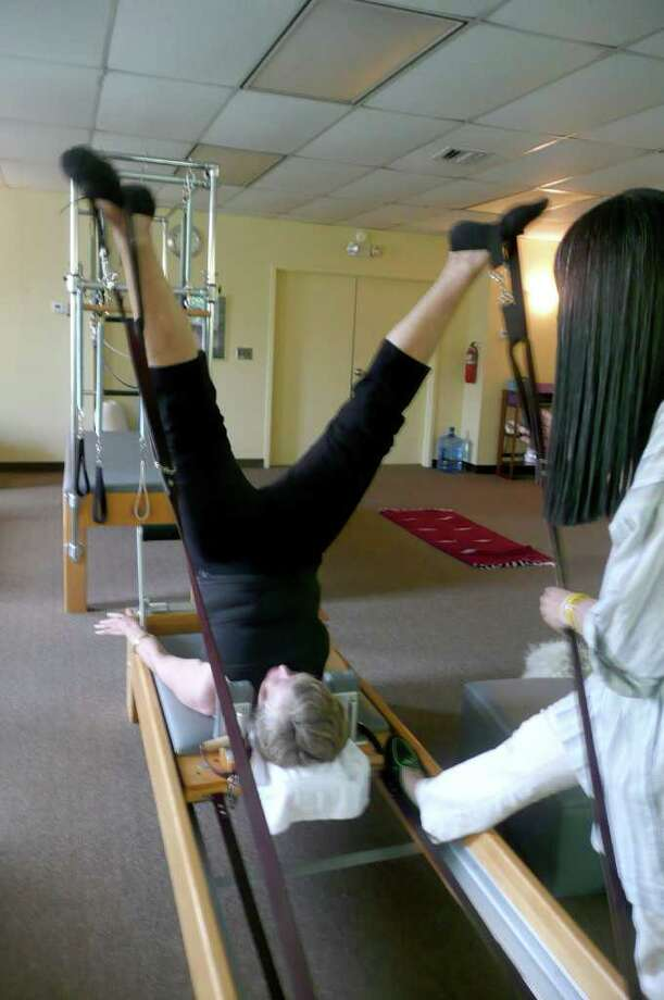 Susan Fisher extends her legs outward, supported by extension straps, while in a shoulder stand with help from instructor Miriam Klinger at Klinger's Greenwich Pilates studio, The Reform School. Photo: Anne W. Semmes