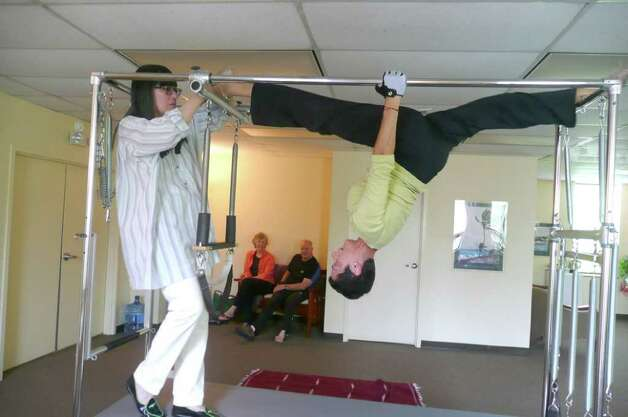 "Instructor Cynthia Peltrow demonstrates the ""Cat"" - an upside down split, which begins from a standing position, with a flip over, using the abdominal muscles - under the watchful eye of Miriam Klinger. Photo: Anne W. Semmes"