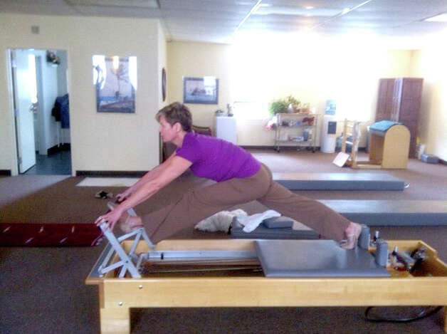"Skier, golfer and runner Barbara Tormandson performs splits on what Pilates instructor Miriam Klinger calls a ""reformer"" apparatus. Photo: Anne W. Semmes"
